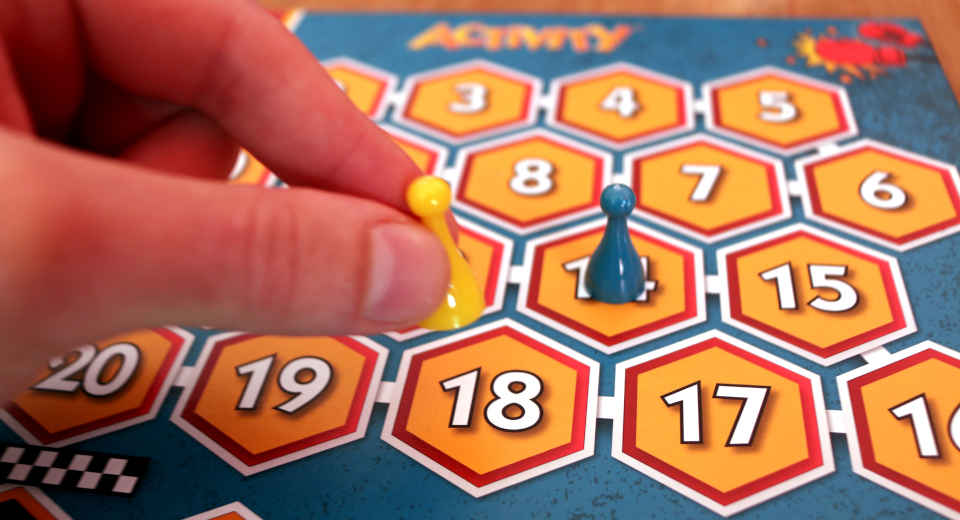 Eine Spielfigur wird auf dem Spielbrett von Activity Knock Out gezogen
